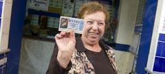 Una mujer muestra un décimo de la Lotería de Navidad.