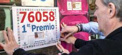 Un lotero cuelga el cartel del Primer Premio