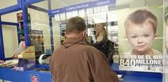 Un hombre compra un billete de Lotería del Niño.
