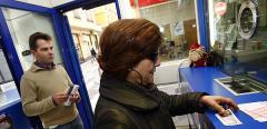 Una mujer compra un décimo de Lotería en una administración.