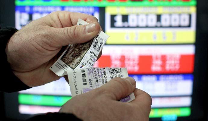 Un hombre rompe un décimo de Lotería.
